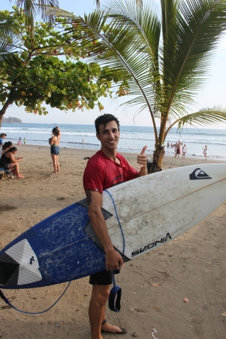 Damian, our front desk manager surfing at sunset at Room2Board Hostel and Surf School
